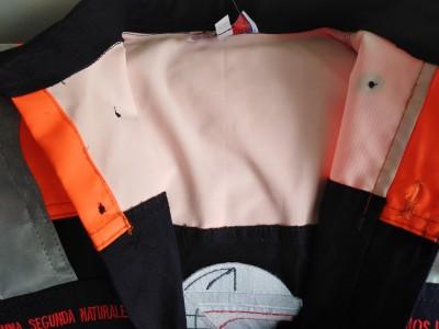 El tejido naranja está cosido sobre el mismo drill de la camisa como un parche